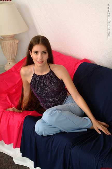 pretty teen female model Lalana with very long hair wearing jeans sitting on a sofa
