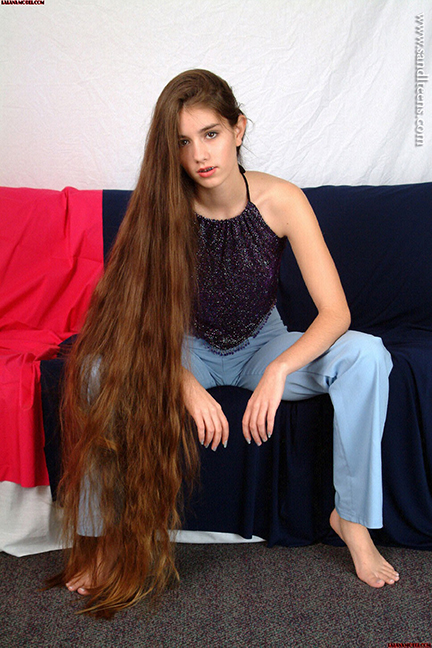pretty teen female model Lalana with very long hair wearing jeans and barefoot sitting on a sofa